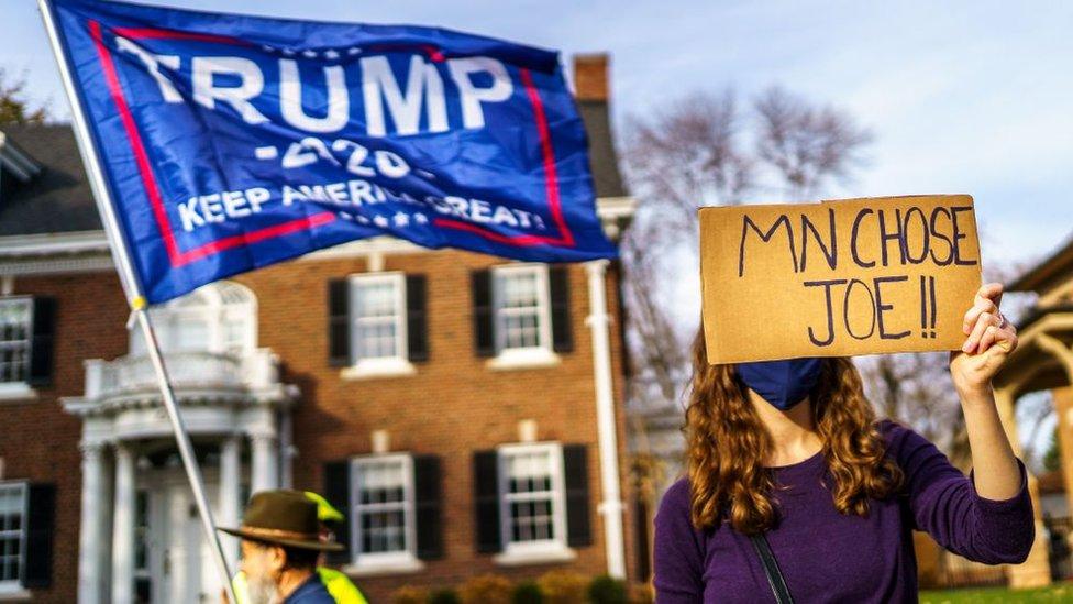 Votantes de Trump y Biden con carteles.
