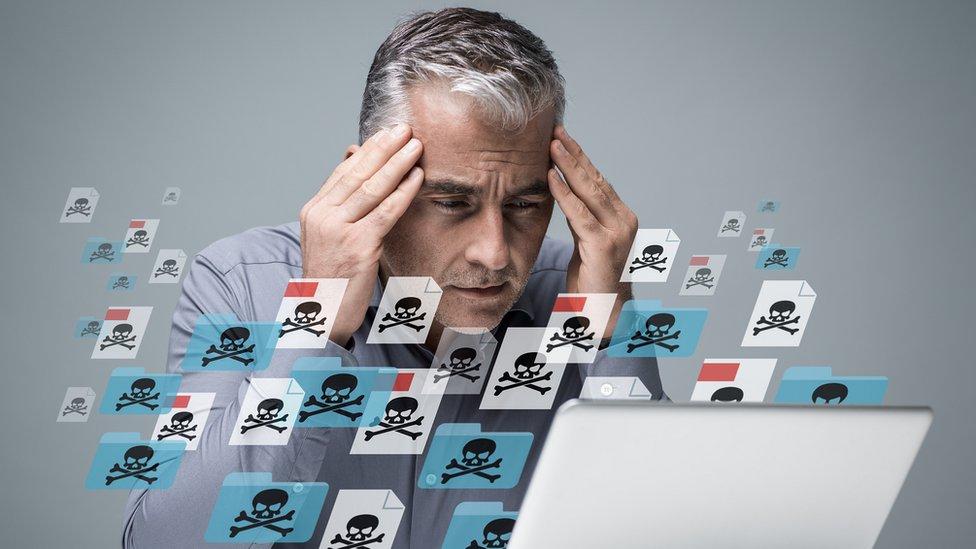 Hombre frente a pantalla de computadora que pareciera infectada de virus.