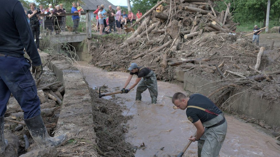Workers clear debris from a channel in a flooded village in western Ukraine, June 2020