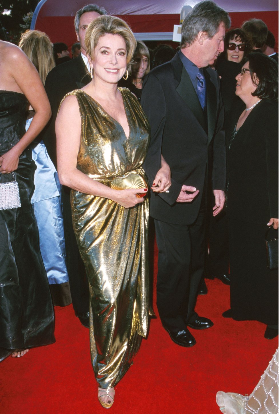 Catherine Deneuve at the Oscars in a long gold evening dress in 2000