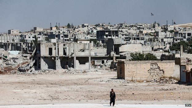 A Syrian man walks in front of destroyed buildings south Kobane, Syria
