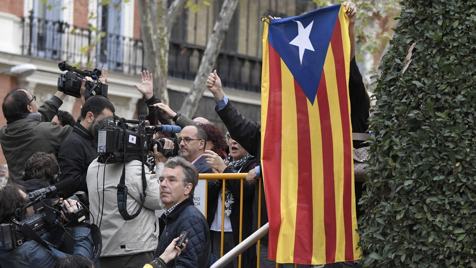 A protester holds a pro-independence Catalan Estelada flag next to journalists as members of the deposed Catalan regional government arrive at the National Court