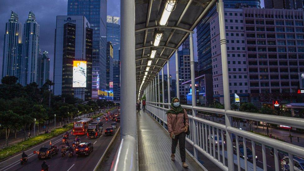 Mujer cruzando un puente en Yakarta