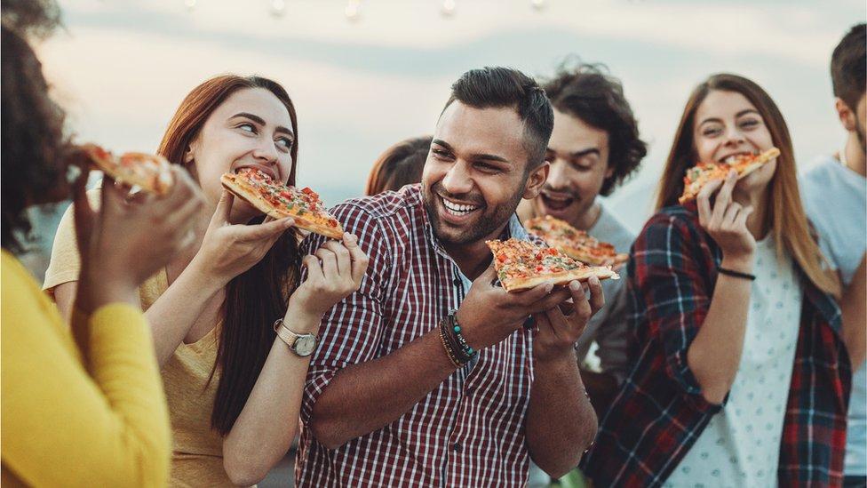 Jóvenes comiendo pizza.
