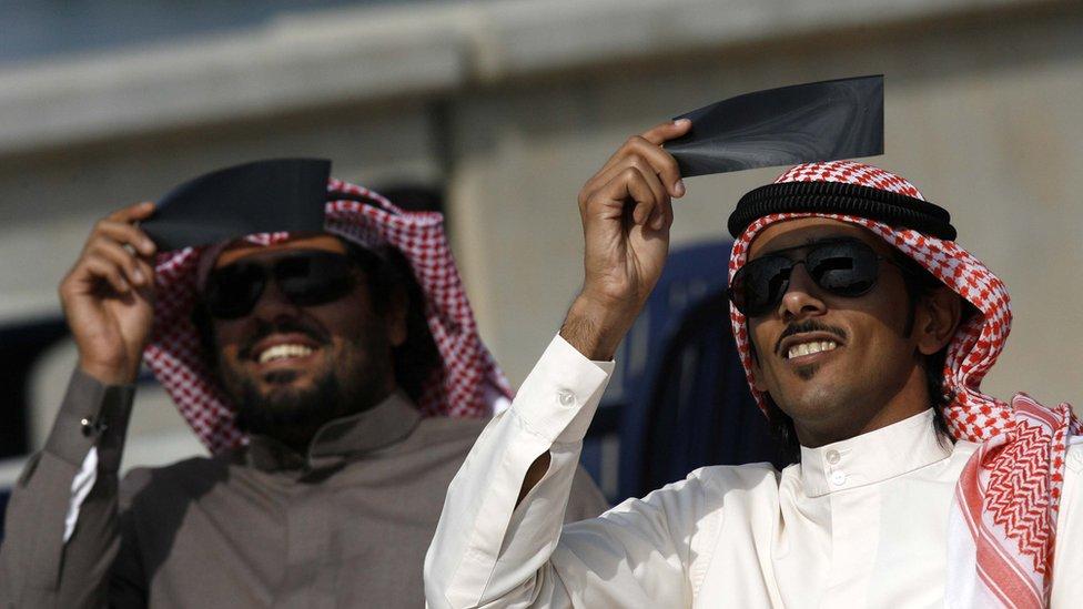 رجلان من الكويت يشاهدان كسوف الشمس - 4 يناير/كانون الثاني 2014