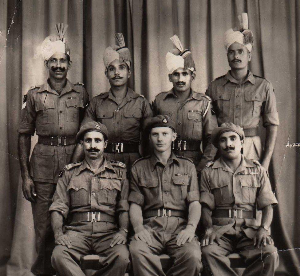 Robin Rowland sentado en el centro con miembros del regimiento de Punjab para una foto después de la derrota japonesa, tomada en Bangkok en 1945.