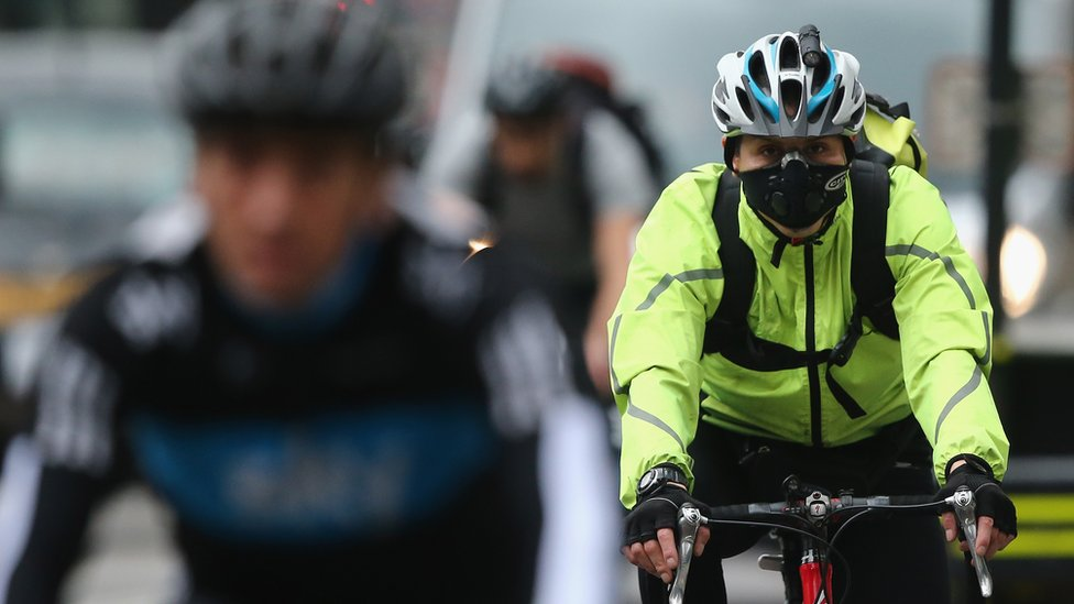 Cyclist wearing smog mask in London traffic