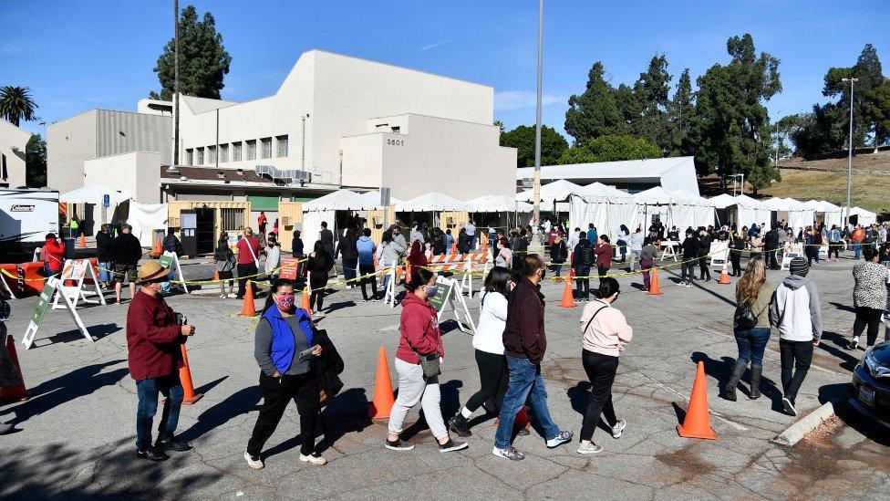 Pessoas com máscaras fazem fila para vacinação em tendas médicas em Los Angeles