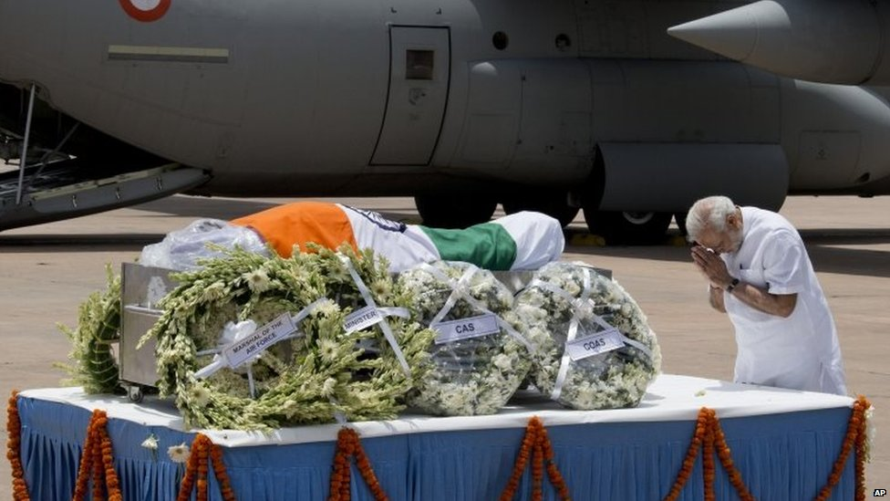 Indian Prime Minister Narendra Modi pays respect after the body of former President A.P.J. Abdul Kalam arrived at the Palam airport in New Delhi, India,