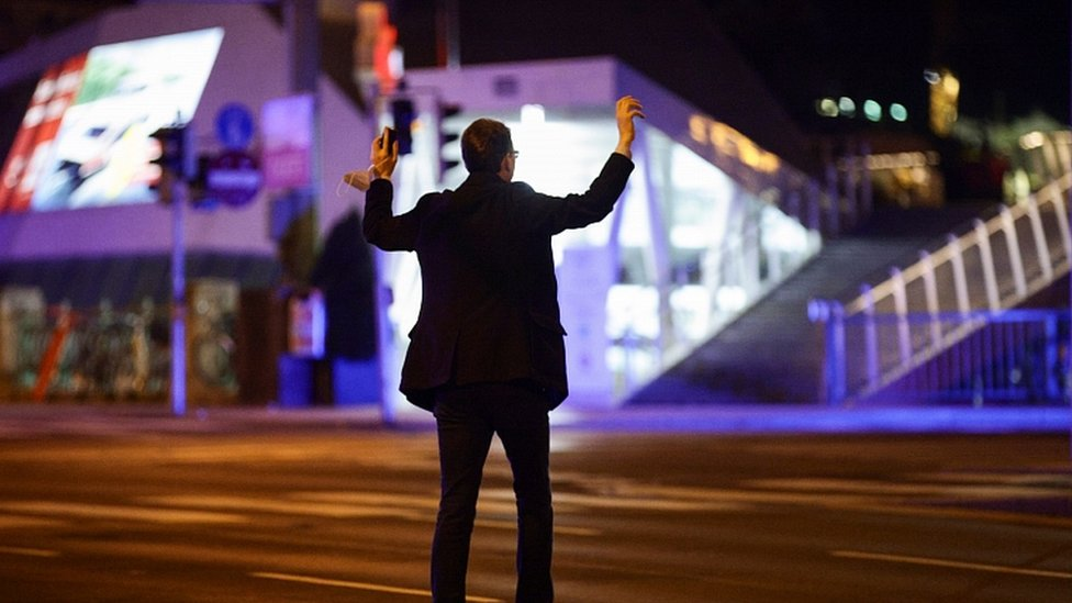 A man holds his hands up as police officers check him on a street after exchanges of gunfire in Vienna, Austria November 2, 2020