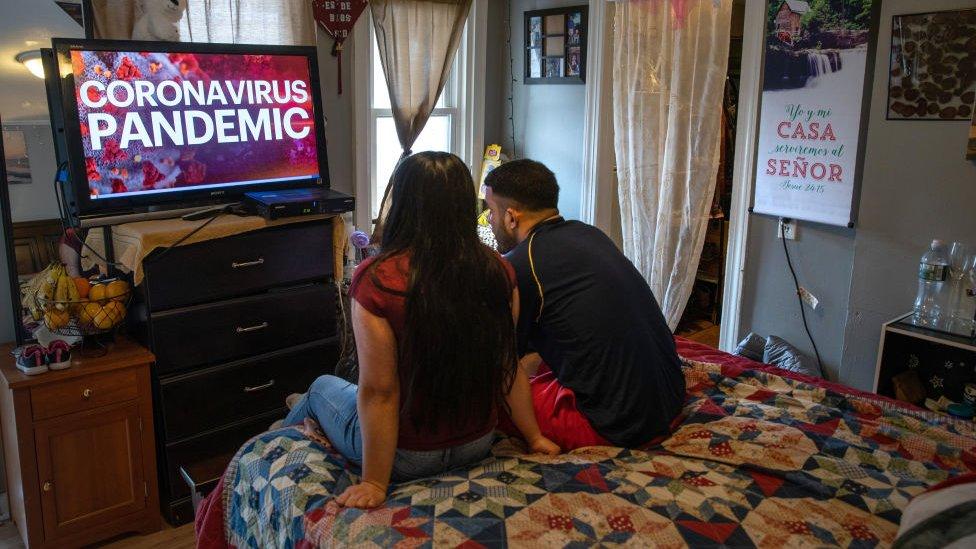 People watch coronavirus coverage on the TV news