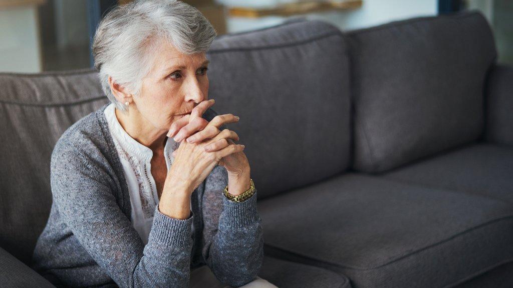 Mujer preocupada en sofá