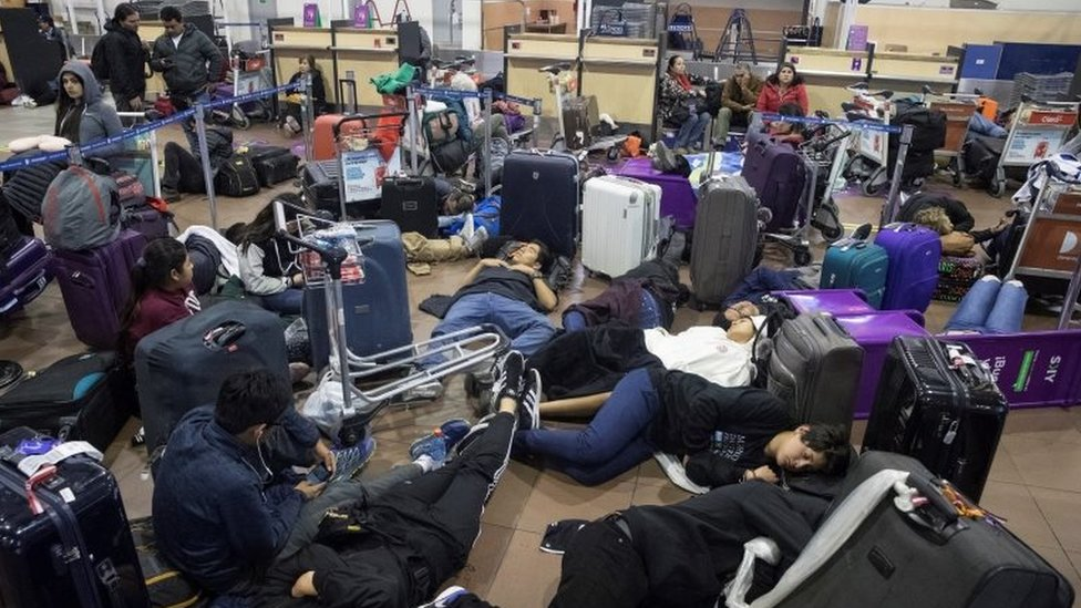 Travellers rest in the Santiago de Chile airport where hundreds of passengers stranded overnight after their flights were cancelled due to curfew imposed in Santiago de Chile