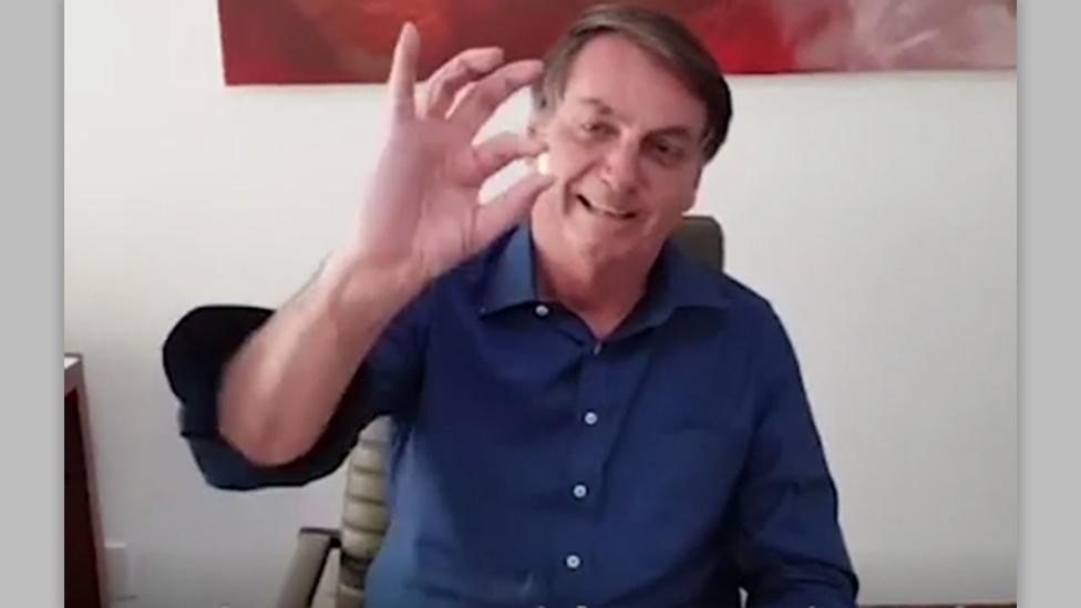 President Bolsonaro sostiene una pastilla de hidroxicloroquina.