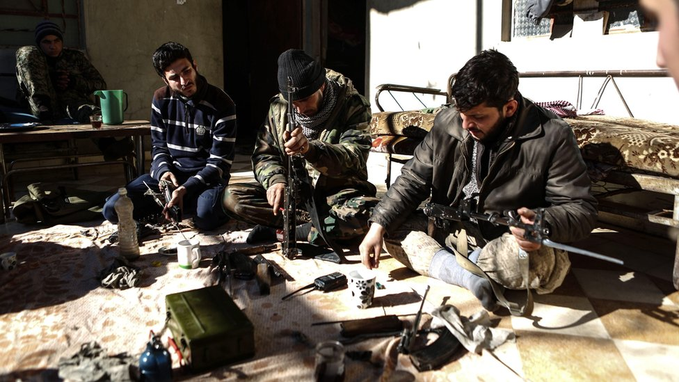 Rebel fighters clean their weapons in rebel-held Douma, on the outskirts of Damascus, Syria (15 December 2016)