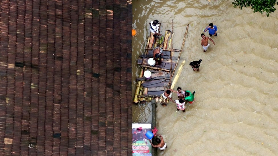 People wait for aid next to makeshift raft at a flooded area in the southern state of Kerala, India,