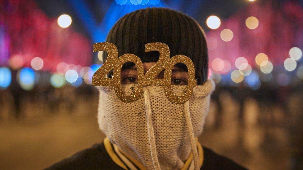 Una persona festeja la llegada de 2020 con lentes 2020.