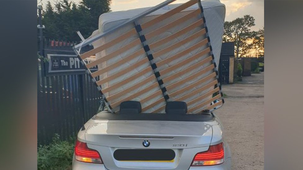 BMW convertible with a double mattress and bed frame sticking out vertically from the back seat.