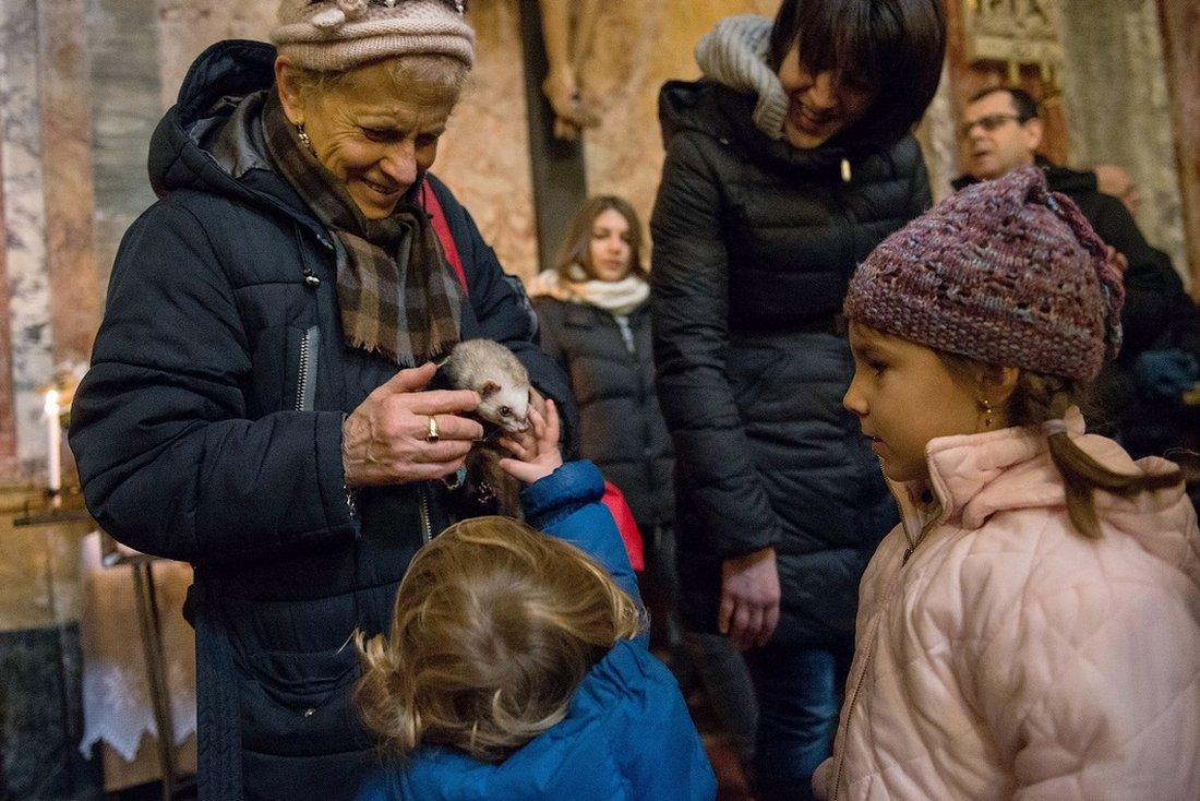 Una mujer muestra su hurón a los niños en una plaza en Italia.