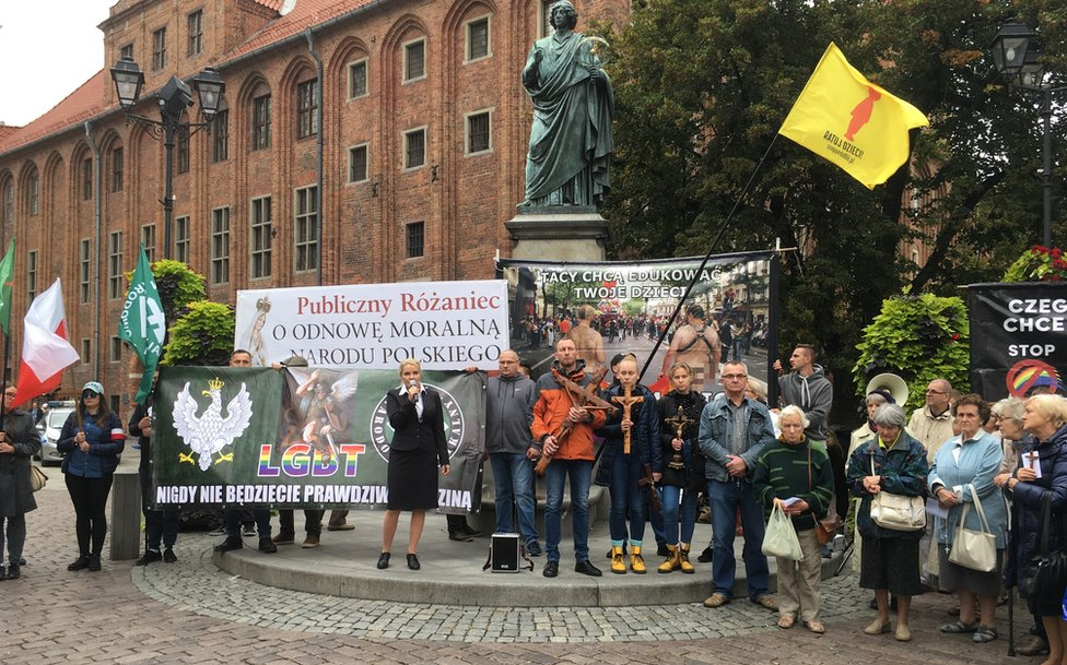 A small counter march in Torun assembled beneath a statue of Copernicus