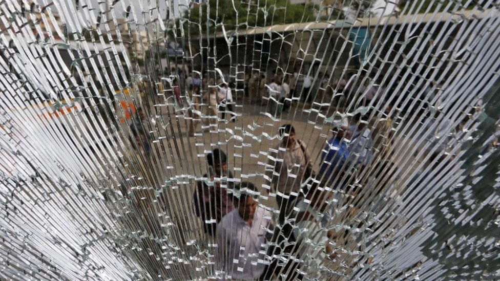 People are seen through the broken glass of a passenger bus that was damaged in clashes between members of the Patel community and the Dalit community during a protest rally in Ahmedabad, India, August 25, 2015