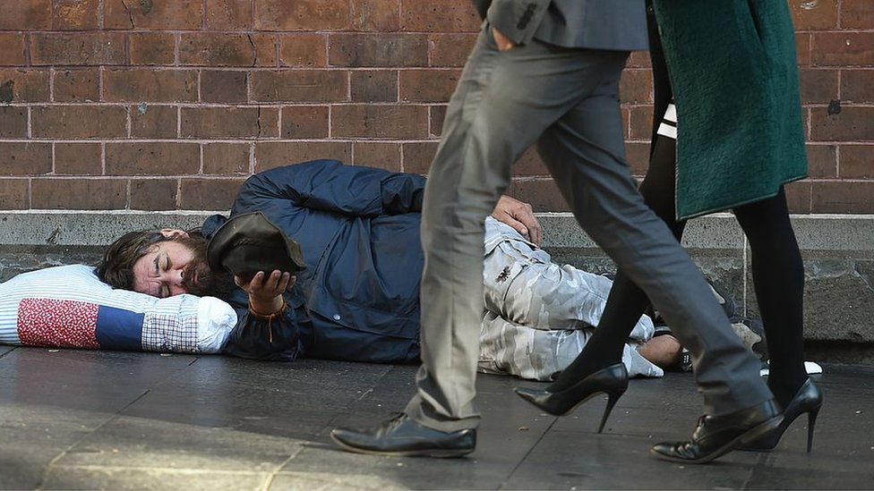 A homeless man begs on the pavement in Sydney's Central Business District