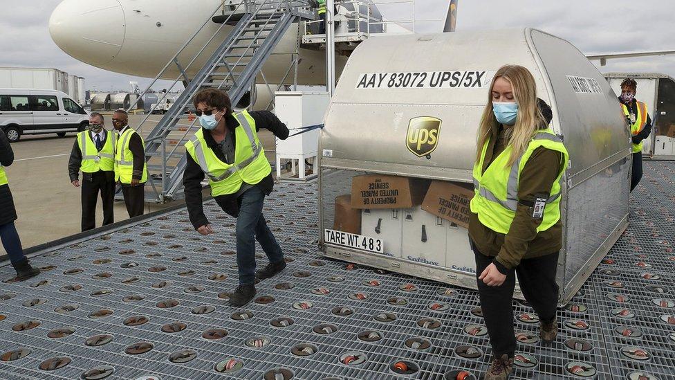 Dois funcionários puxam grande conteiner em pista de aeroporto