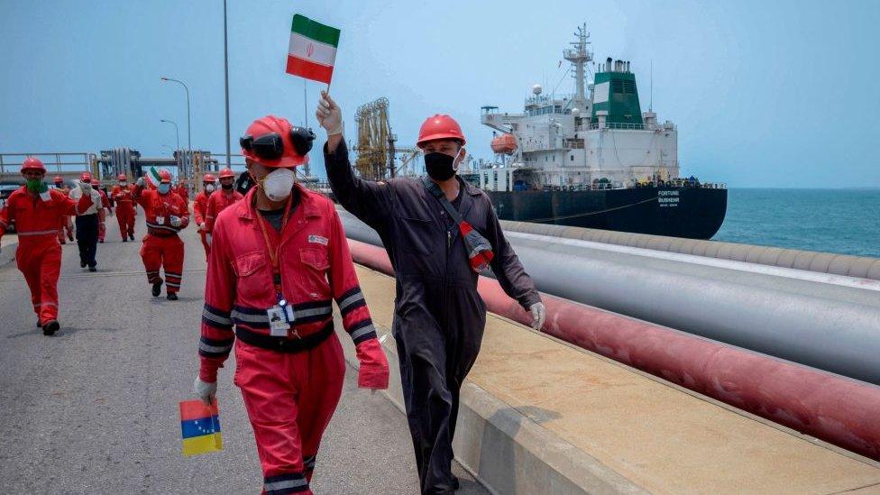 عامل في شركة النفط الفنزويلية الحكومية يلوح بالعلم الإيراني بينما ترسو ناقلة النفط فورتشن التي ترفع العلم الإيراني في مصفاة إل باليتو في بويرتو كابيلو، في ولاية كارابوبو الشمالية، فنزويلا، في 25 مايو/أيار 2020