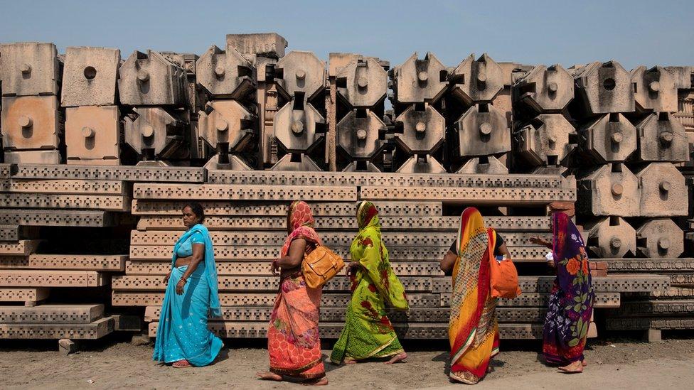 Devotees walk past pillars in the city of Ajodhya, India