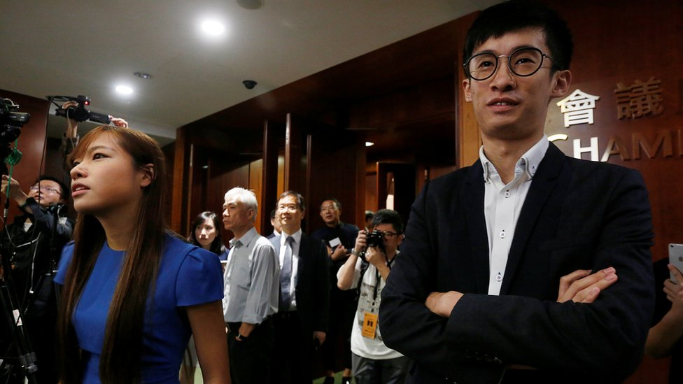 Activists Baggio Leung (R) and Yau Wai-ching (L) stand outside the chamber after pro-Beijing lawmakers staged a walk-out to stall their swearing-in at the Legislative Council in Hong Kong