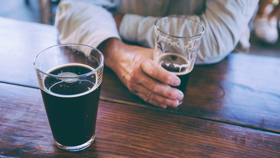 Muškarac pije crno pivo