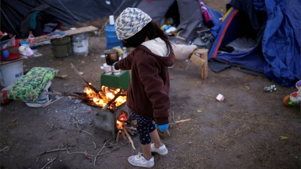 A Mexican girl tries to warm herself by a fire as temperatures dropped in Ciudad Juarez