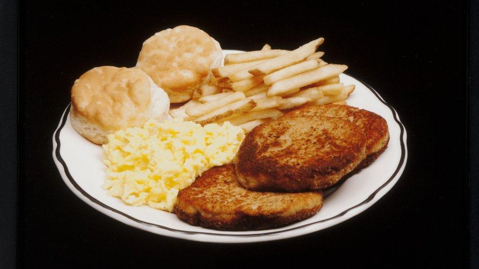 Papas fritas, dos panes dulces, huevos revueltos y tostadas.