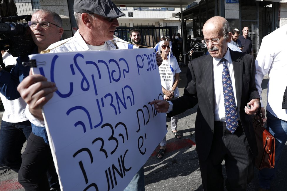 "Benjamin Netanyahu's lawyer, Ram Caspi (right), walks past a man carrying a poster saying ""We support the state prosecutors and the justice system"", as he arrives at the Israeli justice ministry in Jerusalem (2 October 2019)"
