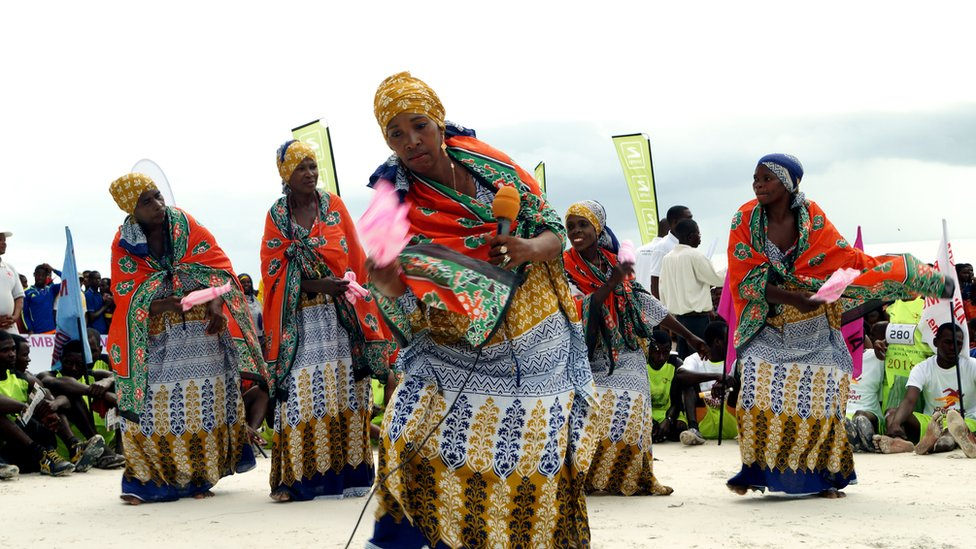 The cyclists finish at Vumawimbi beach with much fanfare. Here, women dance dressed in colourful kangas.