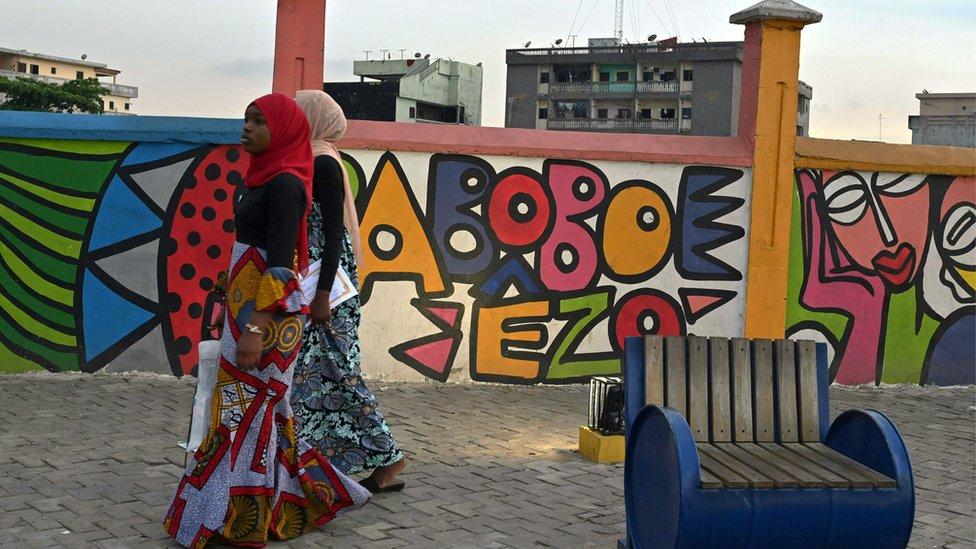 امرأتان تسيران بجانب حائط مغطى بالغرافيتي في حي أبوبو في أبيدجان، عاصمة ساحل العاج الجمعة.