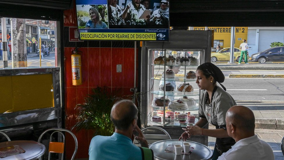 Clientes de un café de Medellín ven la noticia del rearme de Iván Márquez.