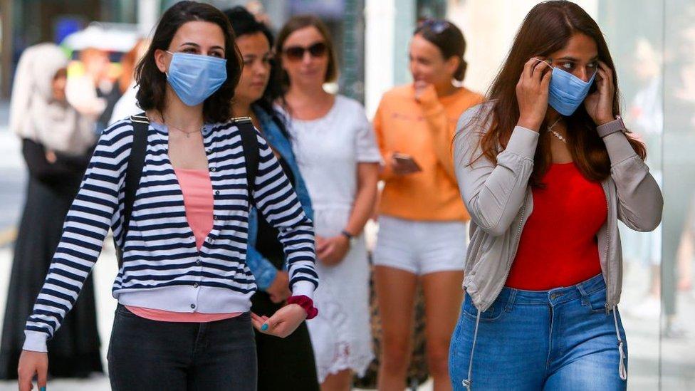 Two women wearing masks in the street