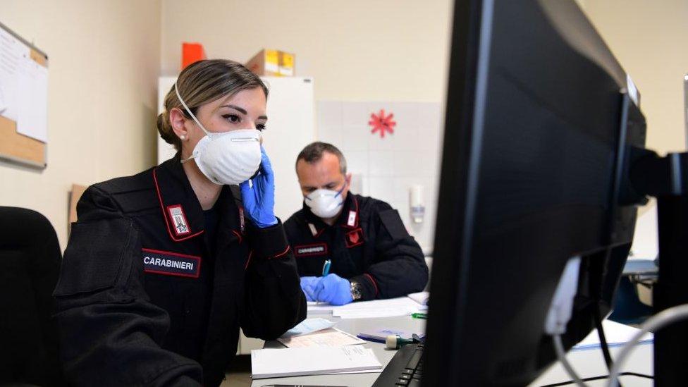 Dos personas con mascarillas en una oficina