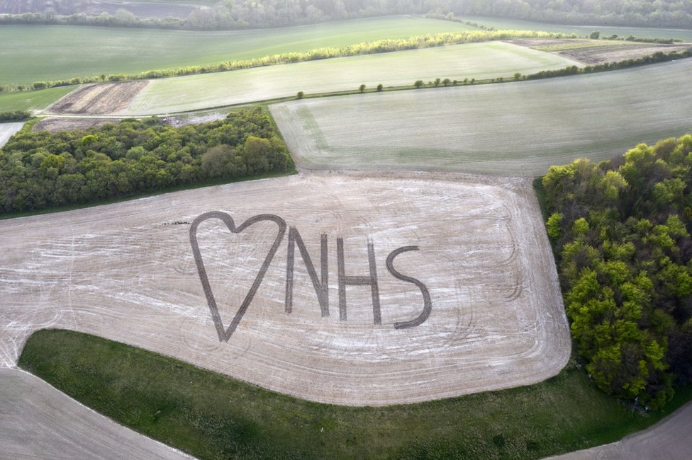 An aerial view on to a field in which NHS and a heart sign has been marked out using crops