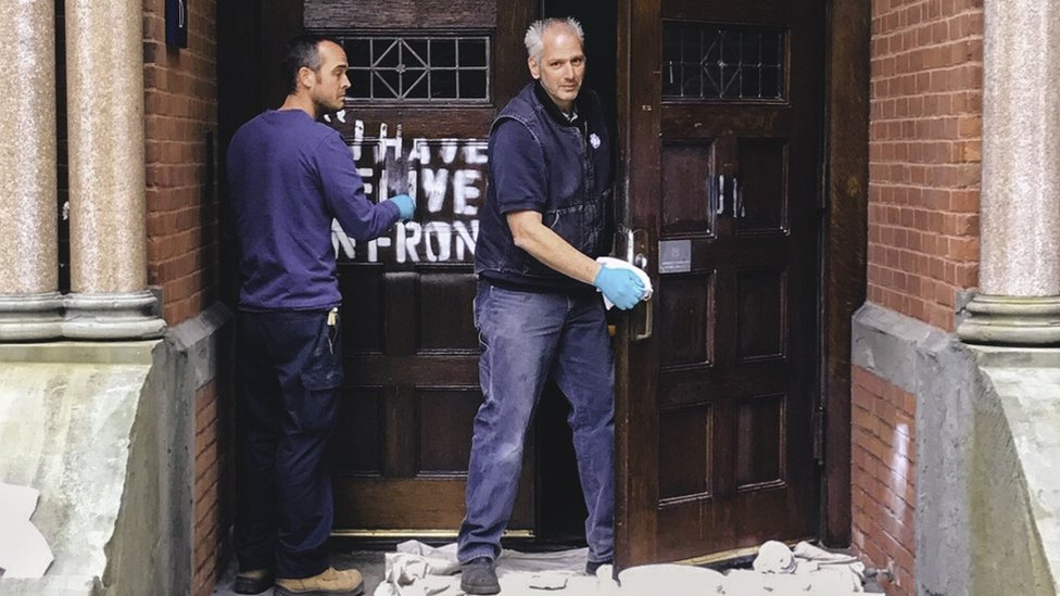 Photo of cleaners removing graffiti from a door