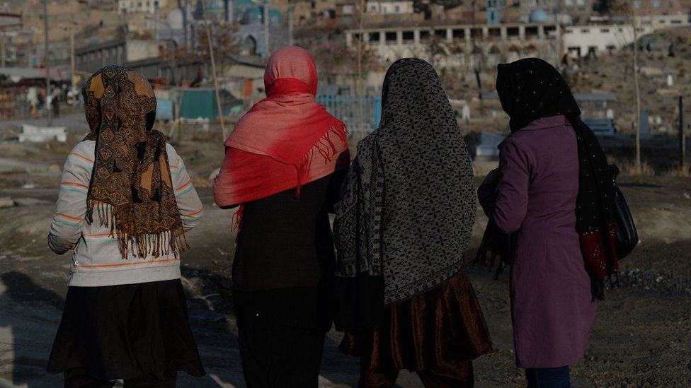 Afghan pedestrians make their way along a street in downtown Kabul on January 14, 2014