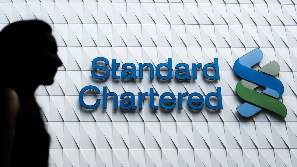 A woman walks past a logo of the Standard Chartered bank in Hong Kong on August 5, 2015