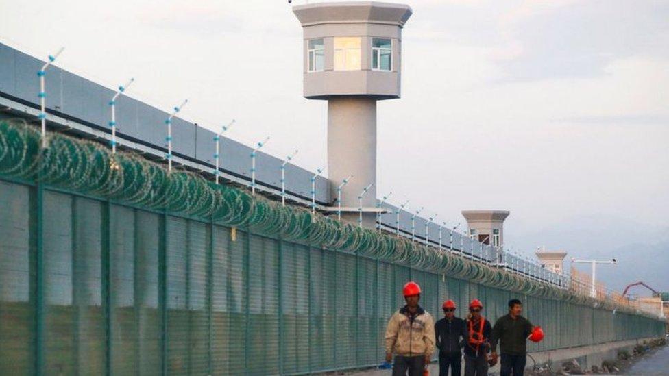 عمال أمام معسكر اعتقال