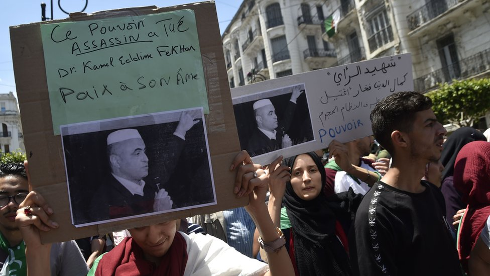 Algerian students hold a sign following the reported death of political activist Kamel Eddine Fekhar, on 28 May 2019