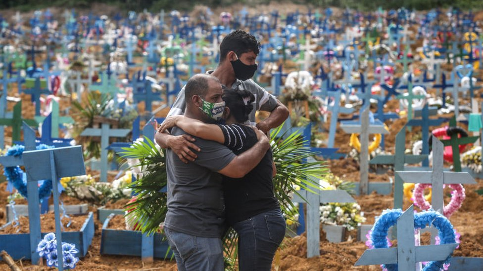 Tres personas abrazándose en un cementerio de Brasil