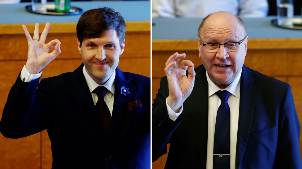 "A composite image shows Martin Helme (L) and Mart Helme make the ""OK"" hand gesture with thumb and forefinger closed, other fingers extended, in a parliament chamber"
