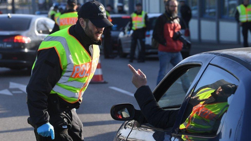 شرطي ألماني يتحدث مع شخص على الحدود الفرنسية الألمانية