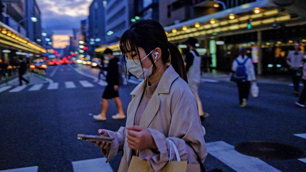Mujer en las calles de Kioto con una máscara protectora