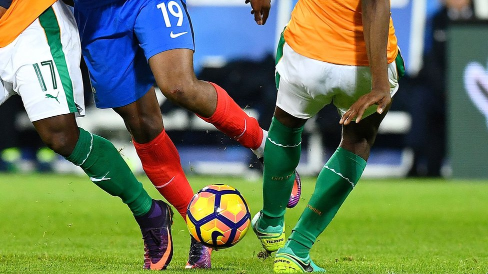 African players in a tangle over a ball